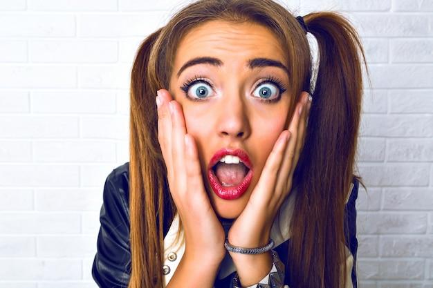 Portret van een vrouw die eng grappig verrast emotionele dagen, twee paardenstaarten en lichte make-up close-up.