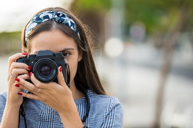 Portret van een vrouw die foto's met haar camera neemt