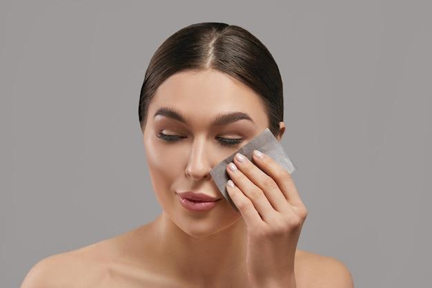 Portret van een vrouw die gezichtsolie vloeipapier gebruikt op een grijze achtergrond