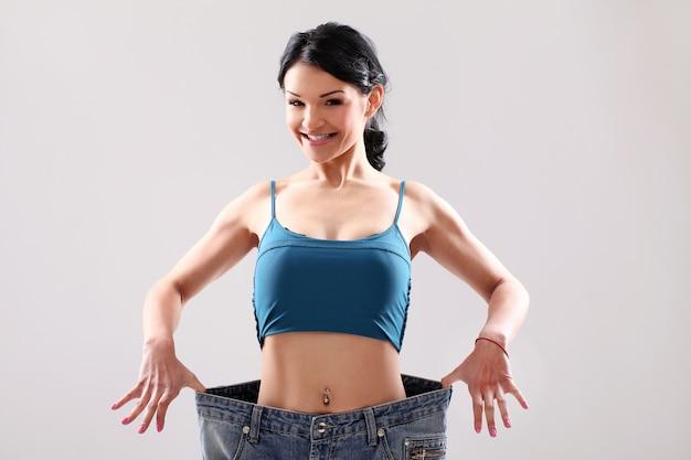 Portret van een vrouw die haar gewichtsverlies toont