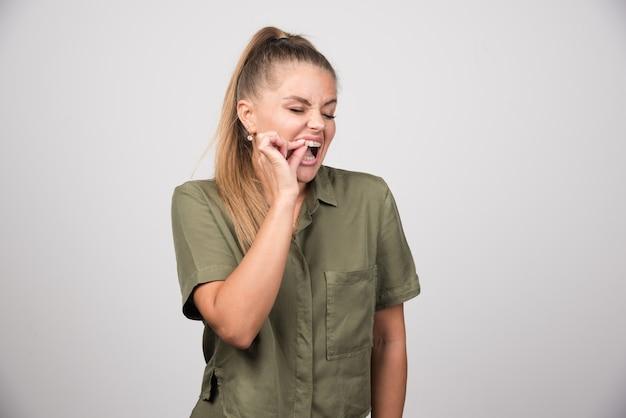 Portret van een vrouw die haar tand aanraakt vanwege pijn.