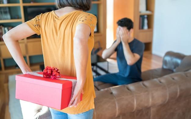 Portret van een vrouw die haar vriend verrast met een cadeautje. viering en valentijnsdag concept.