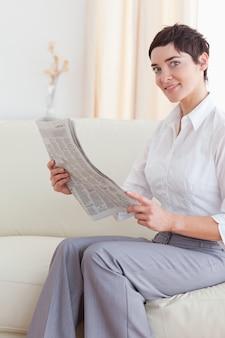 Portret van een vrouw die het nieuws leest onderzoekend de camera