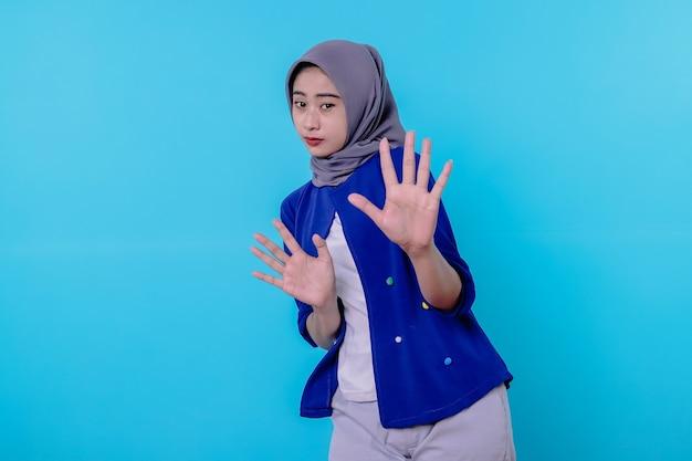 Portret van een vrouw die hijab draagt met stopgebaar op blauwe muur