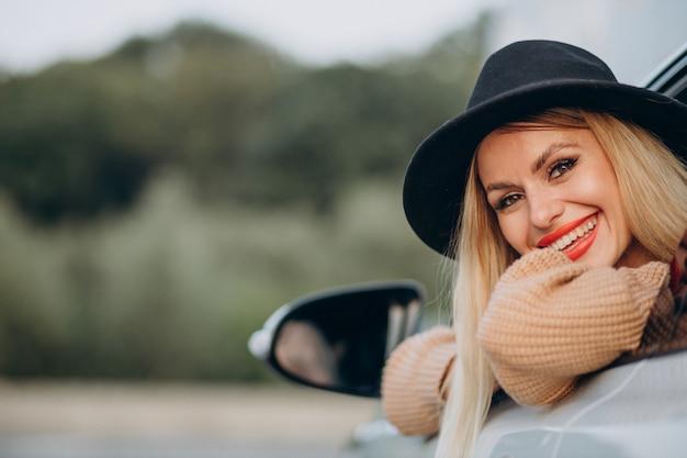Portret van een vrouw die in de auto zit en door het raam kijkt