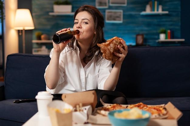 Portret van een vrouw die in de camera kijkt tijdens fastfood lunchmaaltijd bestellen ontspannen op de bank