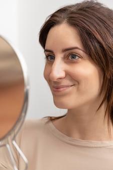 Portret van een vrouw die in de spiegel kijkt na haar microbladingbehandeling