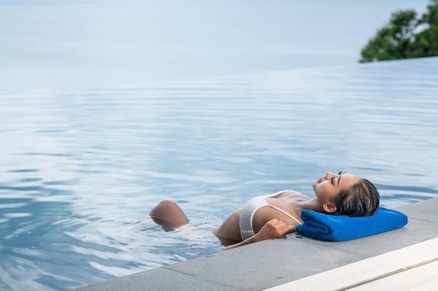 Portret van een vrouw die in het zwembad drijft en haar hoofd op een handdoek laat rusten. ontspan en spa