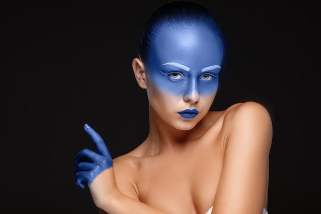 Portret van een vrouw die is bedekt met blauwe verf