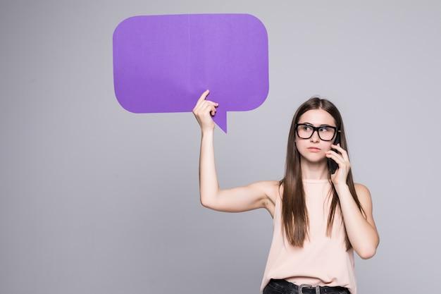 Portret van een vrouw die lege toespraakbel houdt en op mobiele telefoon spreekt dat over grijze muur wordt geïsoleerd