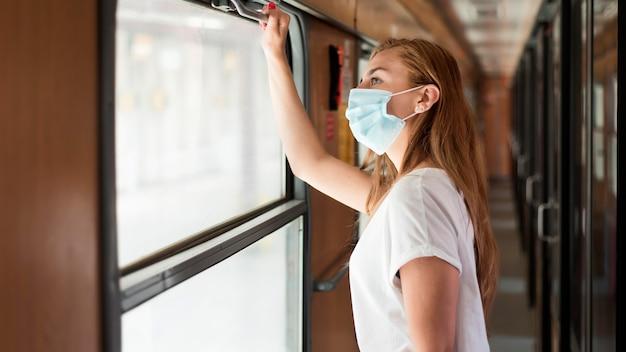 Portret van een vrouw die masker in de trein draagt