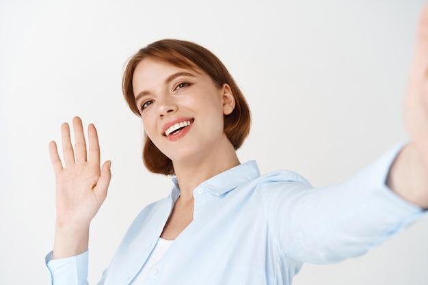 Portret van een vrouw die met de hand zwaait om hallo te zeggen op videochat, smartphone in uitgestrekte hand houdt, vriend begroet, tegen een witte muur staat