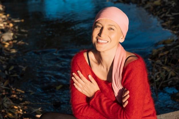 Portret van een vrouw die met een kankersjaal op haar hoofd glimlacht en de camera onderzoekt