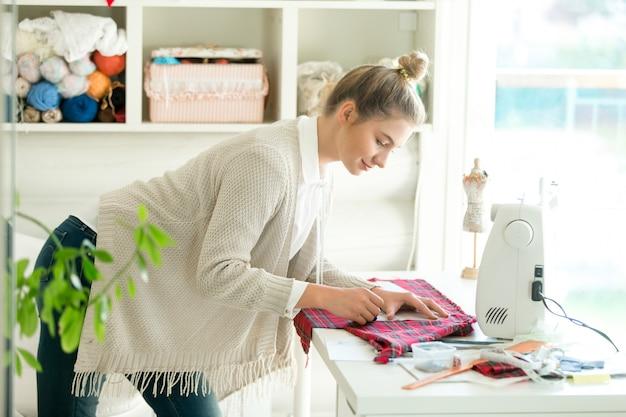 Portret van een vrouw die met een naaienpatroon werkt
