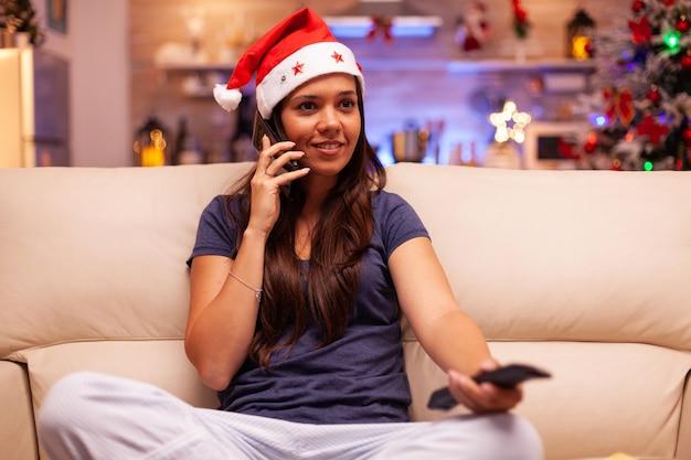 Portret van een vrouw die met een vriend aan de telefoon praat terwijl ze naar een winterfilm op televisie kijkt