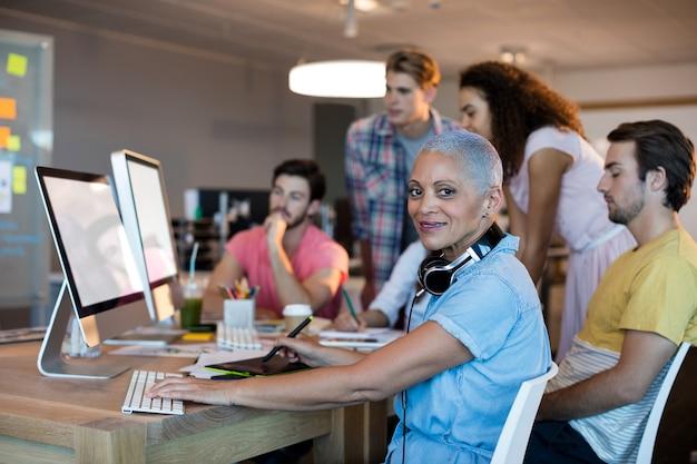 Portret van een vrouw die met haar team op desktop pc werkt