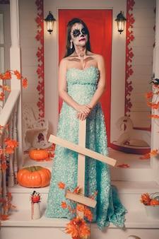 Portret van een vrouw die met spooksamenstelling een houten kruis houdt.