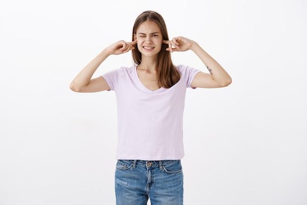 Portret van een vrouw die ongemak voelt door luid verontrustend geluid dat de oren bedekt met wijsvingers die het oog dichtknijpen en op elkaar klemmen terwijl ze een luide knal hoort