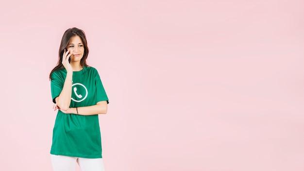 Portret van een vrouw die op cellphone spreekt die whatsapp pictogramt-shirt draagt
