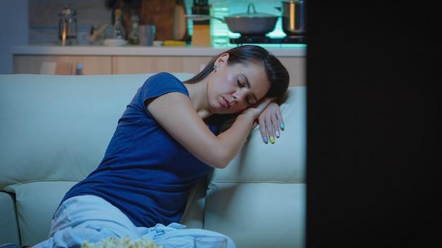 Portret van een vrouw die op de bank slaapt en voor de televisie woont. vermoeide, eenzame slaperige dame in pyjama die in slaap valt terwijl ze op een gezellige bank zit, de ogen sluit terwijl ze 's nachts naar de film kijkt.