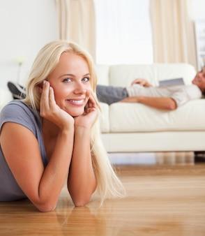 Portret van een vrouw die op de vloer ligt terwijl haar echtgenoot met is