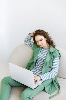 Portret van een vrouw die op een bank zit en op een laptop werkt