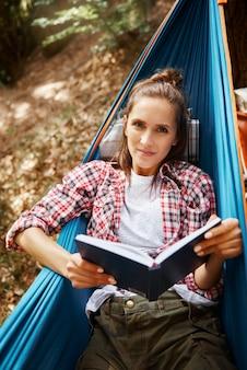 Portret van een vrouw die op een hangmat ligt en een boek leest