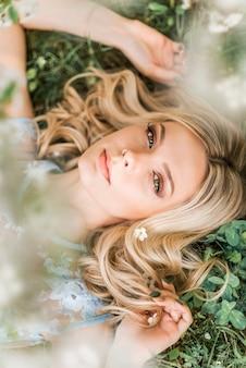 Portret van een vrouw die op het gras in de lente ligt