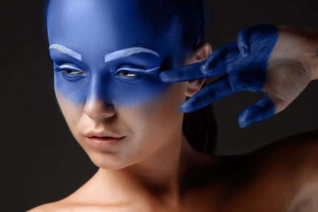 Portret van een vrouw die poseert bedekt met blauwe verf