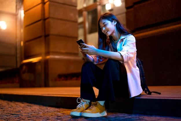 Portret van een vrouw die 's nachts smartphone gebruikt in de stadslichten