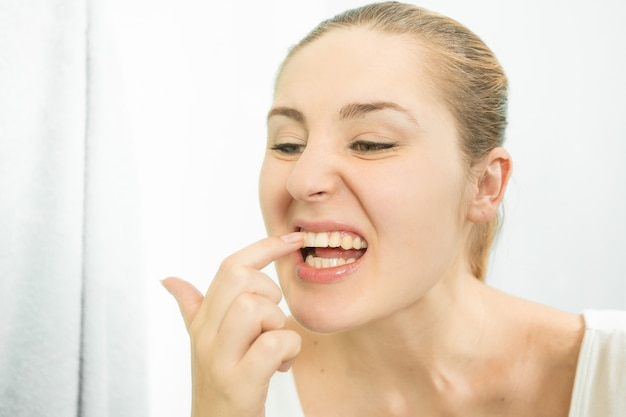 Portret van een vrouw die voedsel plukt dat met haar vinger tussen de tanden zit