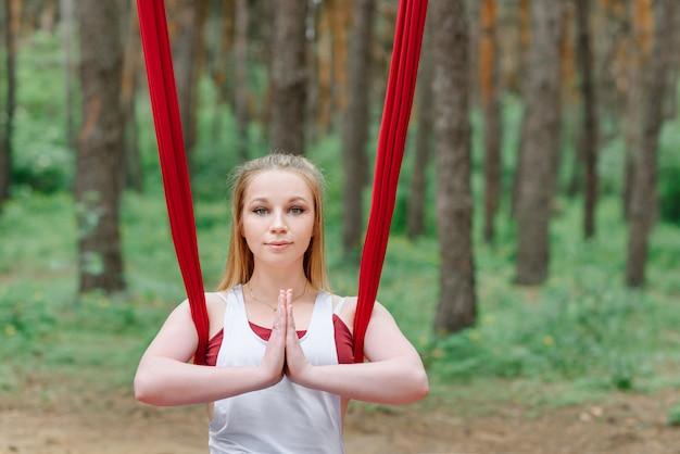 Portret van een vrouw die yoga in het bos doet.