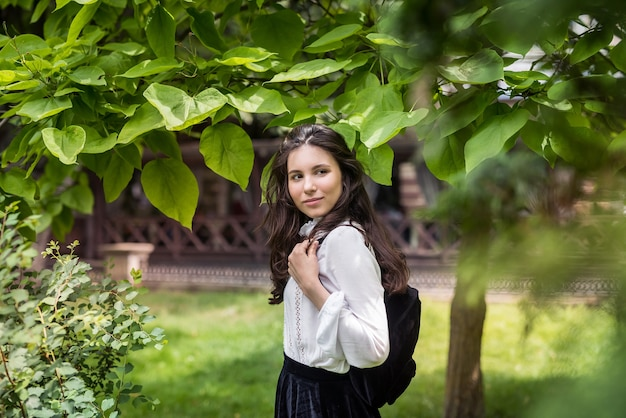 Portret van een vrouw draagt een witte blouse en een stijlvolle zwarte rok in de buurt van een groene boom, stadspark