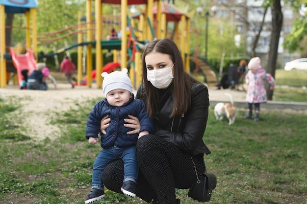 Portret van een vrouw en haar zoon in een beschermend masker tegen het kroonvirus of een uitbraak van het covid-19 en pm 2.5-virus in de stad