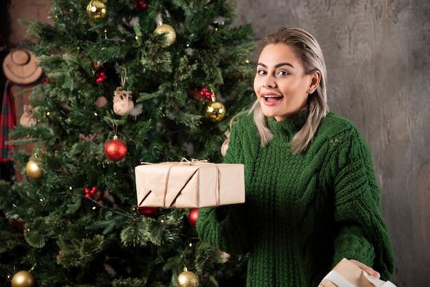 Portret van een vrouw gekleed in groene trui met stapel geschenkdozen en camera te kijken