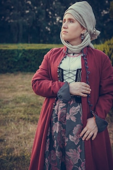 Portret van een vrouw gekleed in historische barokke kleding met een hoofddoek, buitenshuis. middeleeuwse jurk uit de middenklasse
