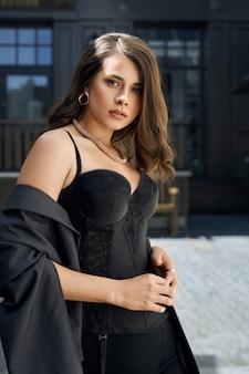 Portret van een vrouw, gekleed in stijlvolle donkere kleding poseren buitenshuis.