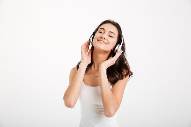 Portret van een vrouw gekleed in tank-top luisteren naar muziek