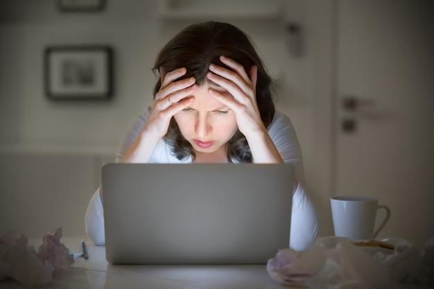 Portret van een vrouw grijpend haar hoofd in de buurt van de laptop