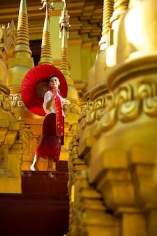 Portret van een vrouw in birmaans nationaal kostuum die zich met een rode paraplu in het midden van vele gouden pagoden bevinden