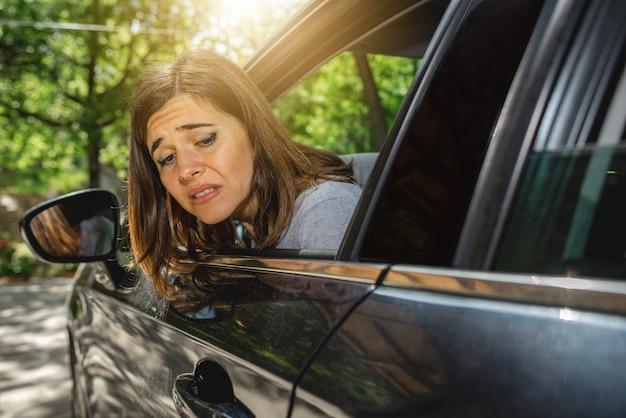 Portret van een vrouw in de auto die uit het raam kijkt met een bezorgd gezicht, misschien omdat de auto tijdens het parkeren of een ongeval op de achterkant is gekrast.