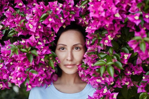 Portret van een vrouw in de takken van een boom met bloemen