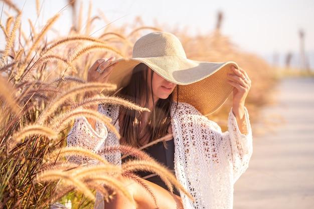 Portret van een vrouw in de zon, zittend in een veld, gekleed in zomerkleren en een hoed.