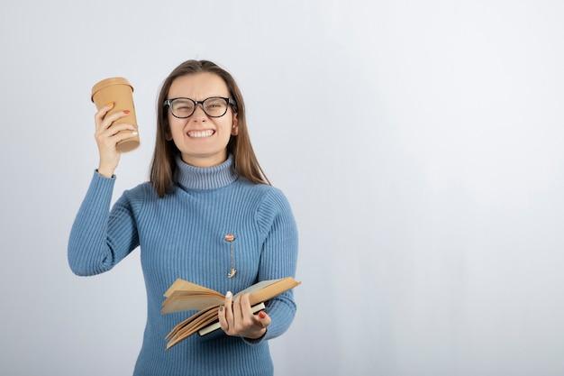 Portret van een vrouw in een bril met een boek en een kopje koffie.