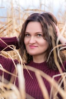 Portret van een vrouw in een bruine trui die poseert in gedroogd gras in een veldvrouw met lang donkerbruin haar