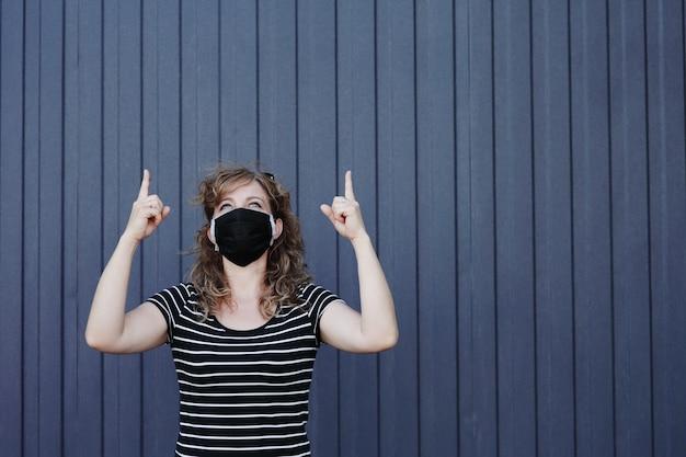Portret van een vrouw in een gezichtsmasker tegen de achtergrond van een donkerblauw gestreepte muur verschijnt