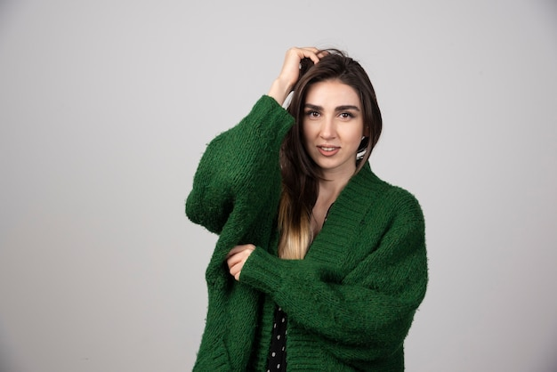 Portret van een vrouw in een groene jas die haar haar aanraakt.