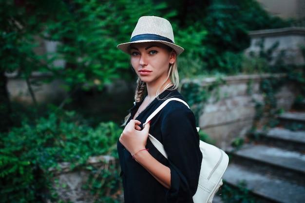 Portret van een vrouw in een hoed met een rugzak op haar rug