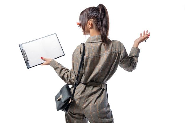 Portret van een vrouw in een levensstijlpak met een tablet en een wit blad in haar hand