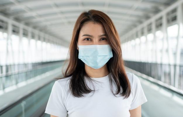 Portret van een vrouw in een medisch masker buitenshuis poseren
